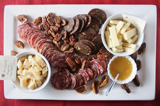 "A delicious antipasti platter featuring extra-old parmigiano-reggiano, fennel-scented salami, fig ""salami"" (figs pressed with spices and nuts), crunchy spicy & sweet pecans, pecorino-romano with honey and oven-roasted figs."