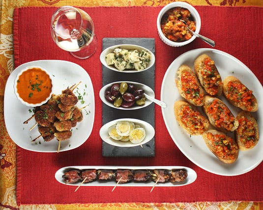 An Assortment of Tapas, Featuring Breaded Mussels Brochettes, Dates Wrapped in Prosciutto, Hard-Boiled Quail Eggs, Marinated Olives, Herbed Cheese and Pisto Croutons