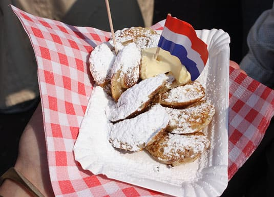 Dutch poffertjes, served with a generous knob of butter and a heavy sprinkling of powdered sugar.