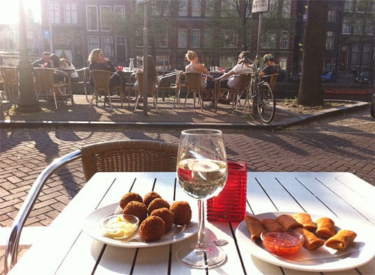 Sunny happy hour by the canal side with white wine and Amsterdam bites.