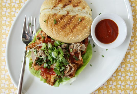 A pulled pork sandwich served on a grilled roll with homemade barbecue sauce, butter lettuce, green onions and coriander.