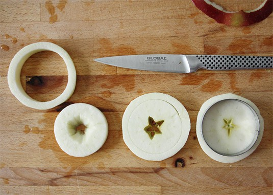 Using a round cookie cutter slightly larger than the bottom of one of the muffin molds, cut out apple rounds, then carefully remove the pits and core, making sure not to break each round.