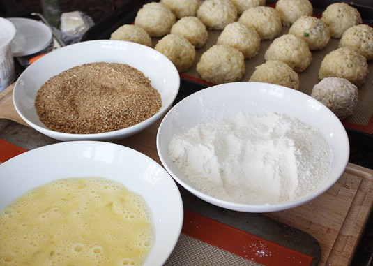 Making Arancine con Ragù: Set three shallow bowls on your workspace. Put the flour in the first bowl, whisk the remaining 2 eggs in the second one, and put the breadcrumbs in the last bowl.