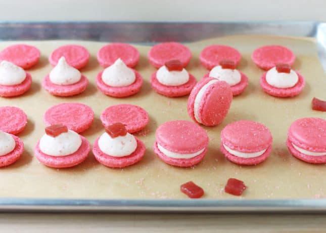 Strawberry and Rhubarb Macarons, filled with rhubarb buttercream and garnished with strawberry and rhubarb pâtes de fruits // FoodNouveau.com